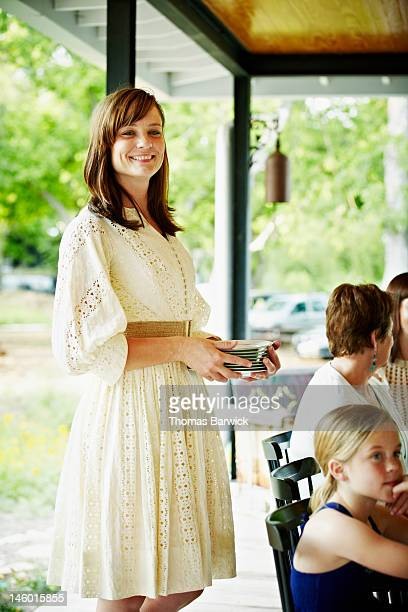 Woman smiling standing holding stack of plates