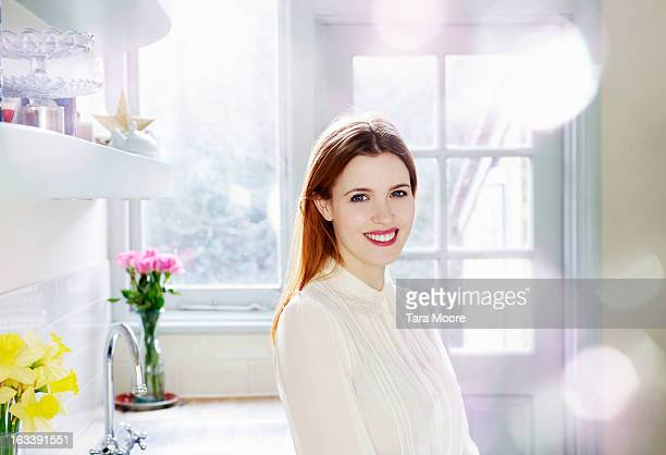 woman smiling to camera in kitchen in morning - white blouse stock pictures, royalty-free photos & images