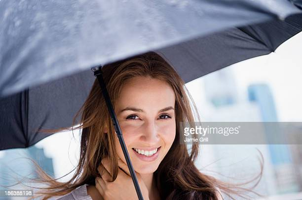 Woman smiling under umbrella