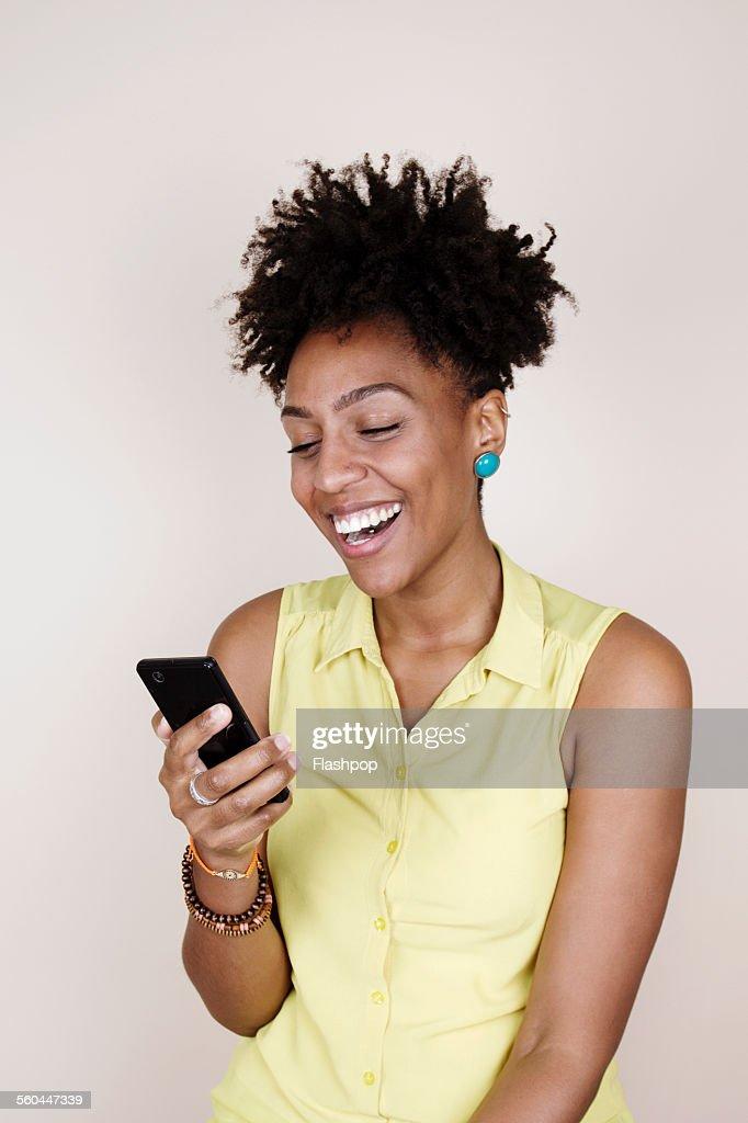 Woman smiling using phone : Foto de stock