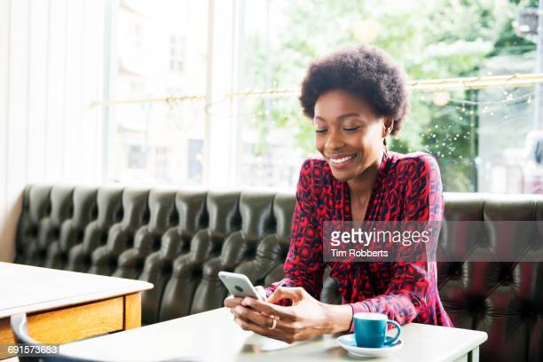 Woman smiling using smartphone at table