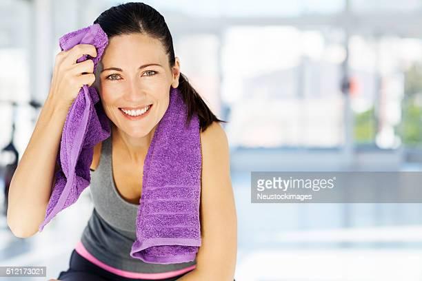 Femme souriant tandis que le nettoyage du front dans la salle de sport Sweat