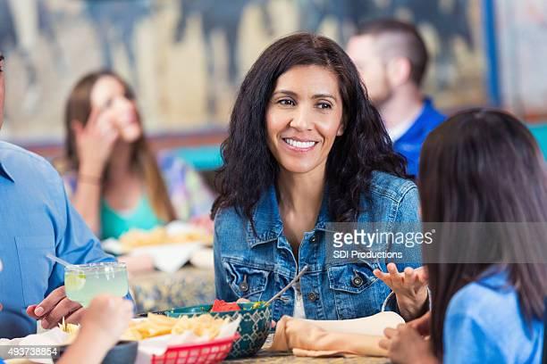 笑顔の女性を楽しみながら、レストランで、ご家族でのお食事
