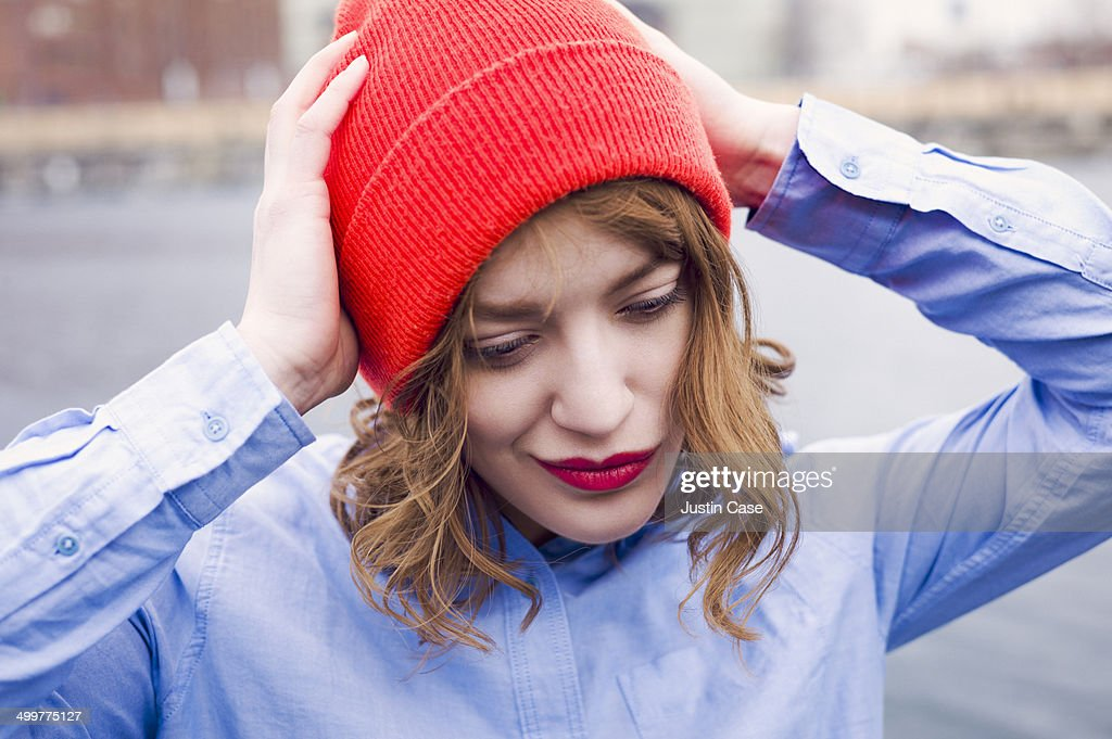 woman smiling while holding her red beany : Stock Photo