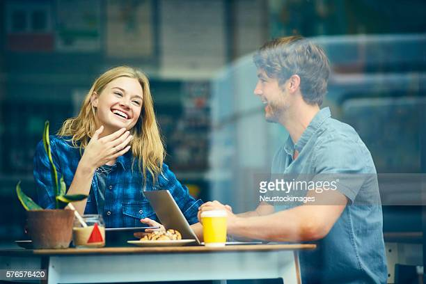 Woman smiling while laughing with boyfriend in trendy cafe