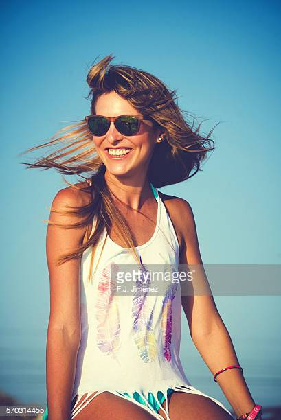 Woman smiling while moving the hair at sunset