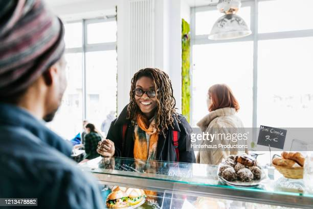 woman smiling while ordering from cafe counter - scarf stock pictures, royalty-free photos & images