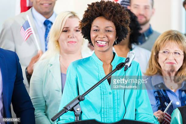 woman smiling while speaking at local political rally or event - local politics stock pictures, royalty-free photos & images