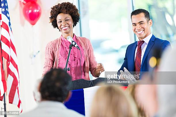 woman smiling while speaking at political rally and supporting candidate - political party stock pictures, royalty-free photos & images