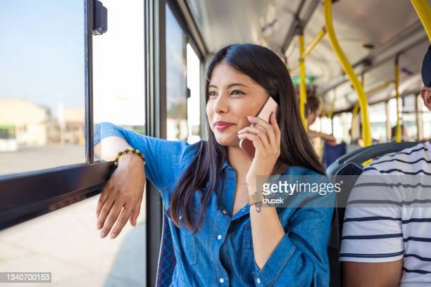 woman smiling while talking on smart phone in bus - izusek stock pictures, royalty-free photos & images
