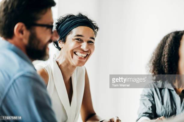 woman smiling while talking with office colleagues - employee stock pictures, royalty-free photos & images