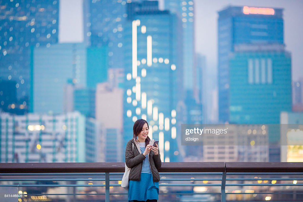 Woman smiling while using smartphone in city : Stock Photo