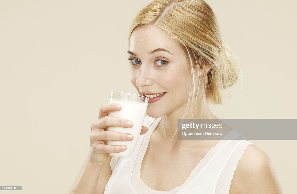 woman smiling whilst about to drink fresh milk : Stock Photo