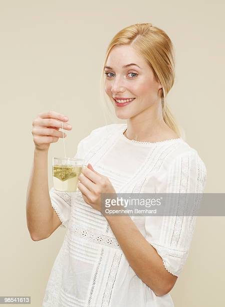 woman smiling whilst dunking tea bag into cup