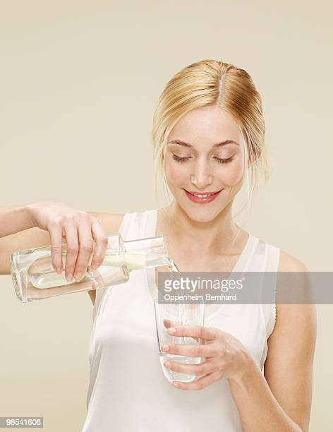 woman smiling whilst pouring a glass of water - fülle stock-fotos und bilder