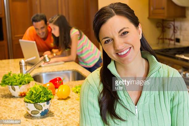 Woman Smiling With Family Using Laptop In Kitchen