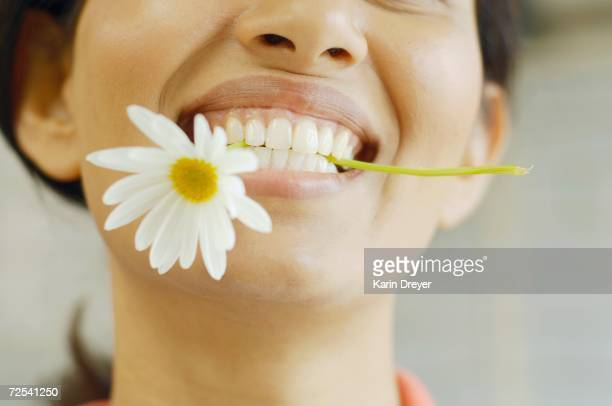 Woman smiling with flower in her teeth