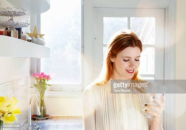 woman smiling with glass of water in kitchen