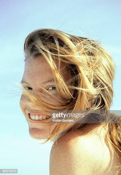 Woman smiling with hair blowing in wind