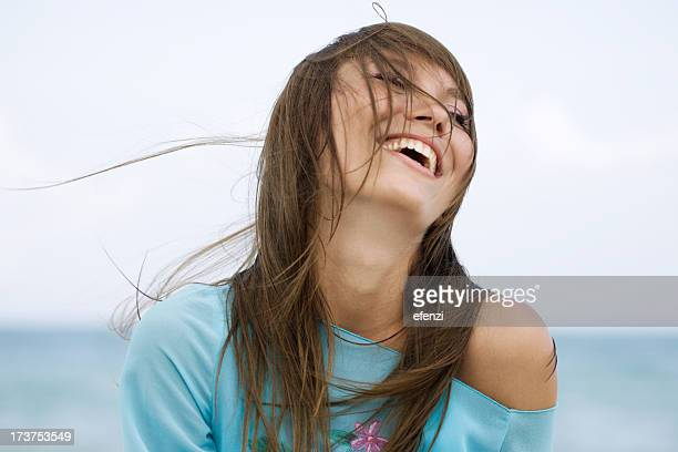 Woman smiling with her hair on her face because of wind