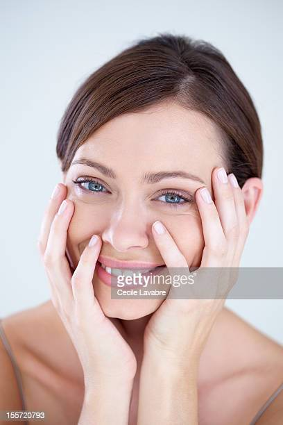 A woman smiling with her hands on her face