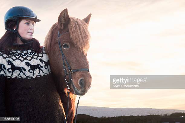 Woman smiling with horse outdoors