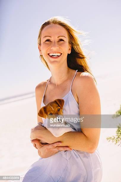 Frau lächelnd mit Welpen in den Armen