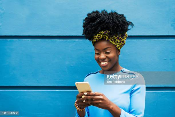 woman smiling with smart phone - hitech moda stock pictures, royalty-free photos & images
