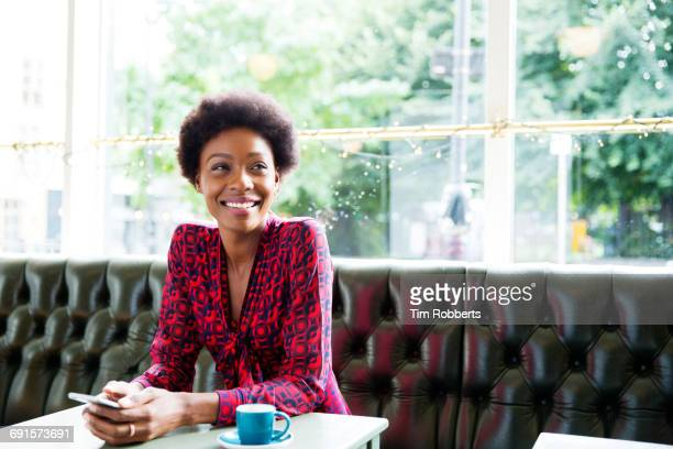 Woman smiling with smartphone, at table