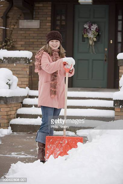 woman smiling with snow shovel in front of house, portrait - snow shovel stock photos and pictures