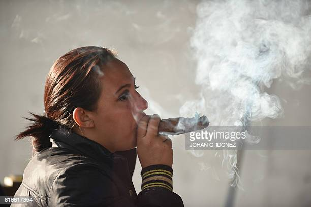 A woman smokes a cigar as she pays homage before an image of San Simon in the municipality of San Andres Iztapa in Chimaltenango some 40 km west of...