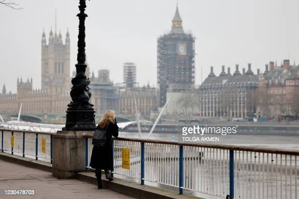 Woman smokes a cigarette as she leans on a railing along the Thames River embankment in central London on January 8 as England entered a third...