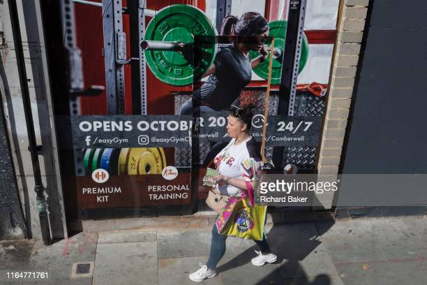 A woman smokes a cigarette as she walks past an ad for a forthcoming easyGym in Camberwell south London on 29th August 2019 in London England