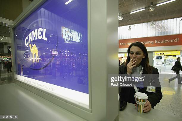A woman smokes a cigarette December 13 2006 at Frankfurt airport Germany Chancellor Angela Merkel is scheduled to meet with German state governors...