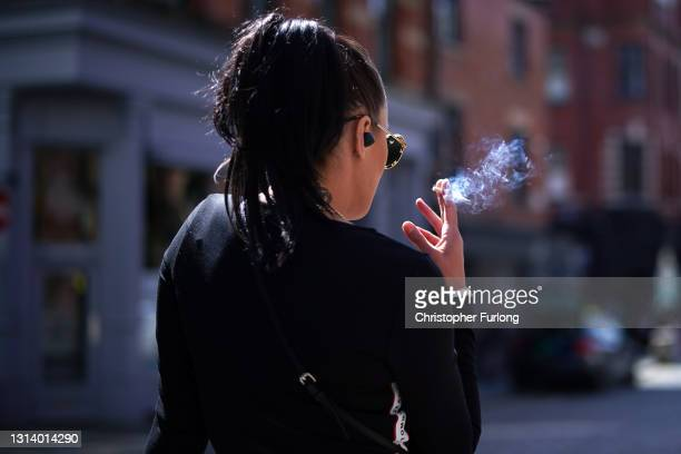 Woman smokes a cigarette in the spring sunshine as pandemic lockdown restrictions ease in Manchester's Northern Quarter on April 23, 2021 in...