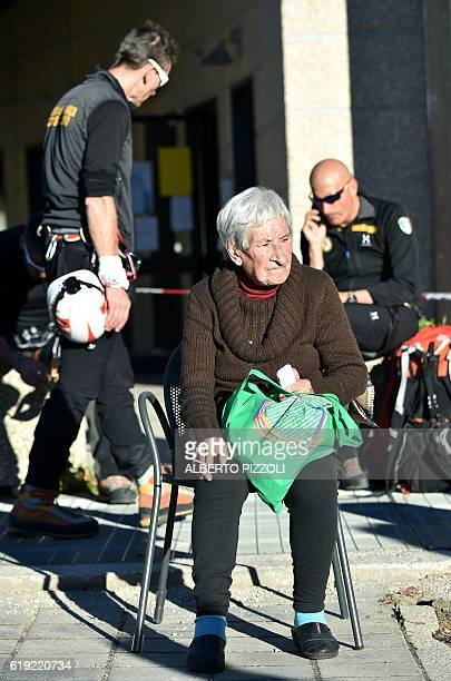 A woman smokes a cigarette near rescuers outside the center of Norcia following a 66 magnitude earthquake on October 30 2016 It came four days after...