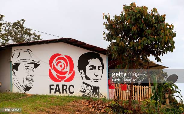 A woman smokes a cigarette outside her house which has a mural depicting Revolutionary Armed Forces of Colombia leader Simon Trinidad in prison in...