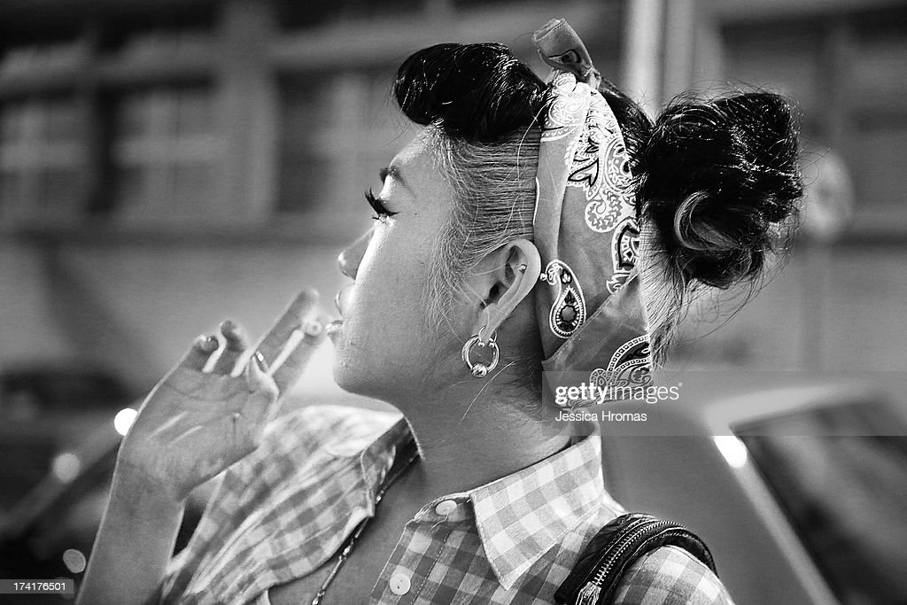 A woman smokes a cigarette outside the Fringe Club during the Dirty Boogie Rockabilly Festival on July 20, 2013 in Hong Kong, Hong Kong.