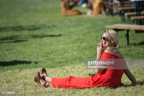 A woman smokes a cigarette prior to the Met horse race one of the richest horse races on the African continent at Kenilworth race track on January 27...