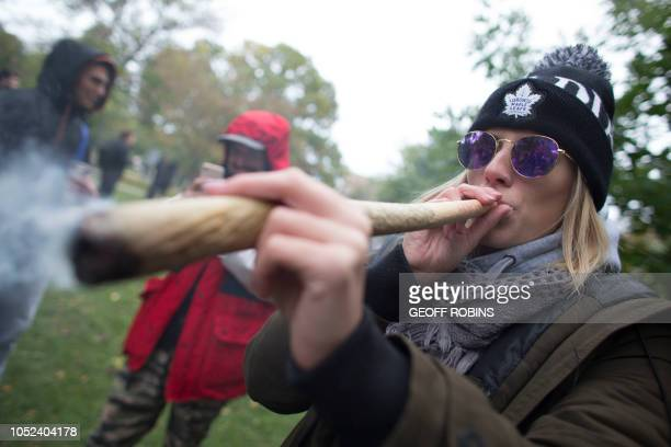 TOPSHOT A woman smokes a marijuana cigarette during a legalization party at Trinity Bellwoods Park in Toronto Ontario October 17 2018 Nearly a...