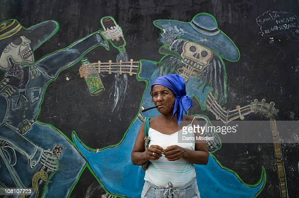 A woman smokes a pipe in the National Cemetery in PortauPrince Haiti Haitians celebrate the Catholic All Saints' Day Nov 1 and festivities continue...