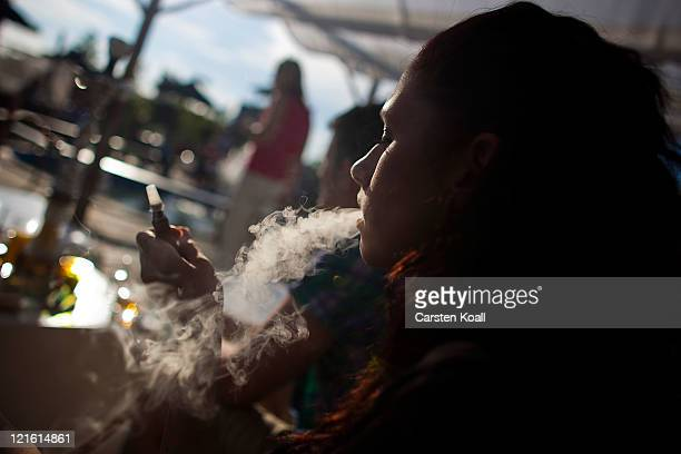 A woman smokes a shisha in the beach bar Bundespressestrand on August 20 2011 in Berlin Germany Berlin which is among Europe's most popular travel...