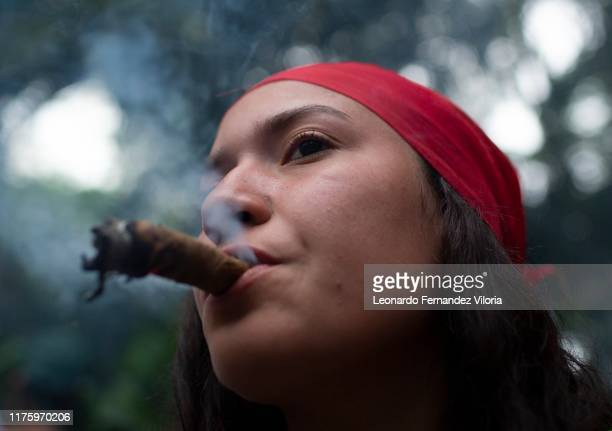 A woman smokes a tobacco to ask María Lionza for her entrance to the mountain and to be able to pay her offering during a congregation of thousands...