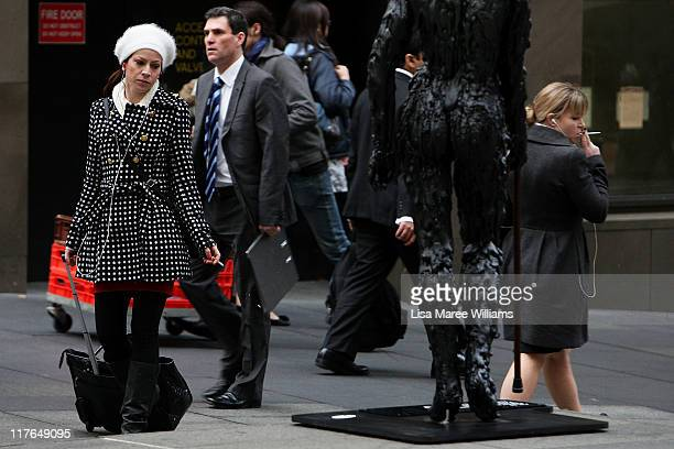Woman smokes amongst tar figures placed in the CBD to raise awareness about the damage smoking causes to the body at Martin Place on June 30, 2011 in...