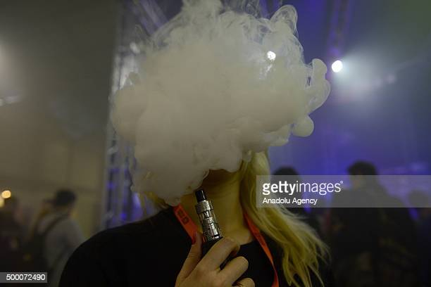 A woman smokes an electronic cigarette during the Vapexpo 2015 Moscow at Sokolniki Exhibition Center on December 05 in Moscow Russia