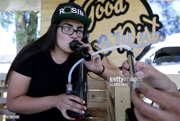A woman smokes from a pipe during the first Cannabis Cup where selfcultivation and the quality of the herb are encouraged in Tlajomulco de Zuniga...
