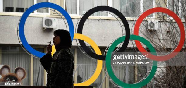 Woman smokes in front of the Russian Olympic Committee headquarters in Moscow on November 26, 2019. - Russia's anti-doping chief said on November 26,...