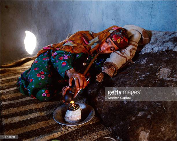 A woman smokes opium to ease her rheumatism in Issik Afghanistan