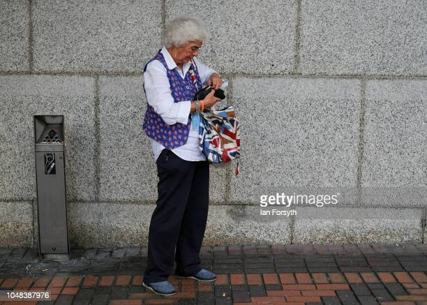 A woman smokes outside the International Convention Centre on day three of the Conservative Party Conference on October 2 2018 in Birmingham England...