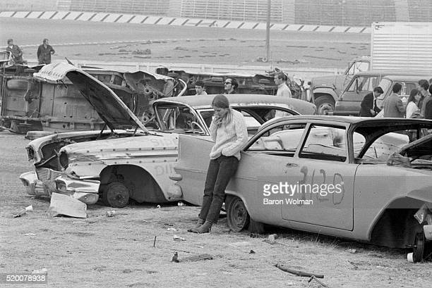 A woman smokes surrounded by derelict cars at the Altamont Speedway Free Festival in Northern California held on Saturday December 6 1969